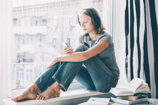 tonåring tittar i mobilen